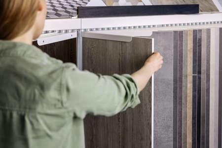 woman looking at laminate material samples in interior design shop Standard-Bild