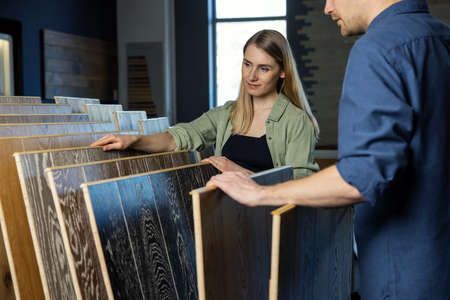 young couple choosing wood texture laminate floor from samples in flooring store for house improvements Standard-Bild