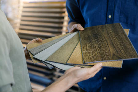 seller showing wooden texture laminate material samples to customer