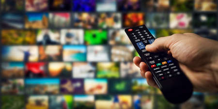 tv channels in background and remote control in hand. smart television and content on demand concept Standard-Bild
