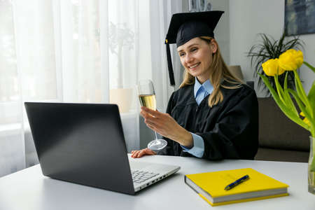online graduation celebration - happy woman using laptop and drinking champagne together with university friends Standard-Bild