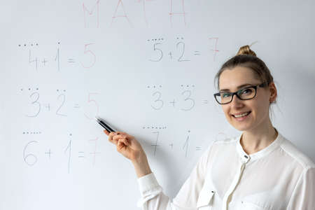 math teacher explaining primary school basic mathematics on whiteboard in classroom