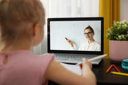 distance learning - primary school teacher explaining basic mathematics online. little girl using laptop at home. math lesson Standard-Bild