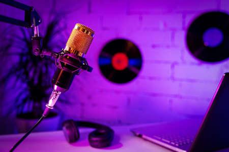 recording podcast - microphone headphones and laptop in home studio. neon lights Standard-Bild