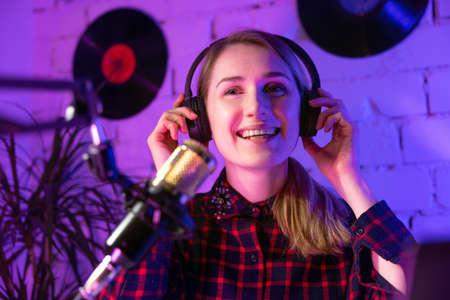 happy woman radio host with headphones broadcasting in studio
