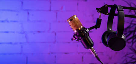 stand with microphone and headphones on brick wall background. online radio and podcasting concept. sound recording. copy space