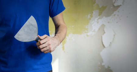 construction worker standing with putty knife in hand on old wall background. banner copy space