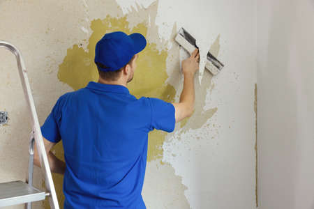 worker removing old painted wallpaper from the wall. house renovation interior renewal