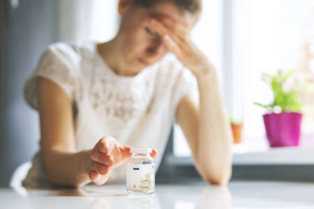 woman with headache reaching for painkiller pills. migraine, cephalalgia and stress concept