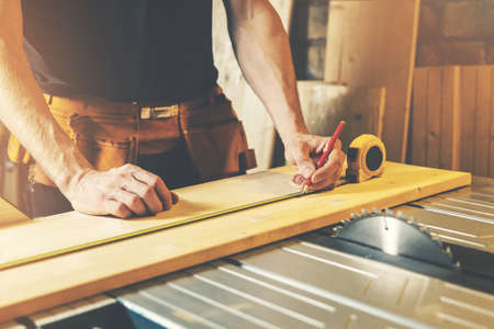woodworking workshop - carpenter measure and mark the wooden plank for cutting