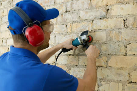 worker cleaning old brick wall with rotary wire brush