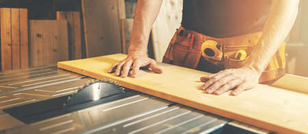 cutting wooden board on a table saw. woodworking and carpentry. furniture manufacturing