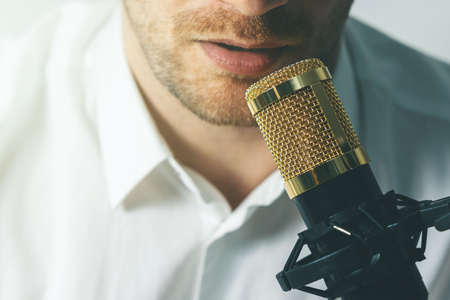 young man recording podcast. speaking in microphone closeup Standard-Bild