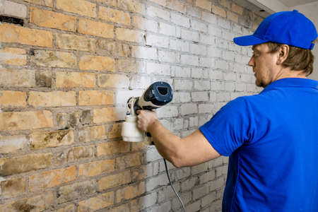 construction worker painting old brick wall in white color with paint sprayer