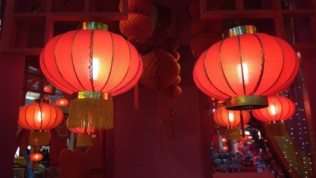 A Pair of Red Lantern Hang on Ceiling with few at the background Stock Photo