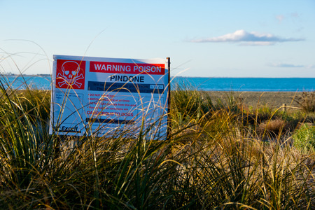 Warning poison signboard at the sea side with blue sky