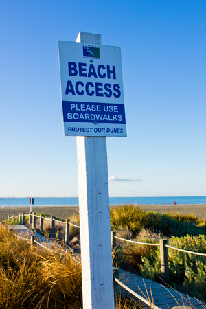 Beach access signboard at the sea side with blue sky