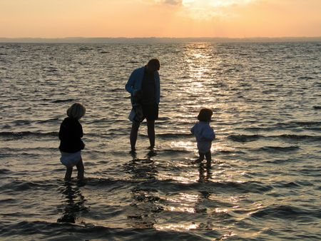 - father and girls play in the water in sunset time photo