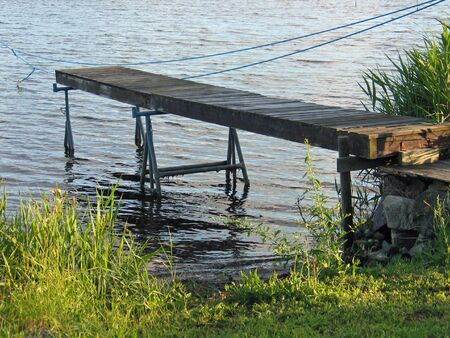 rowboats: Small homemade wooden jetty dock in front of the water
