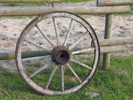 An old wooden wheel of a wagon leans on a ranch fence Stock Photo - 1786923