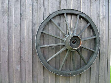 Wooden wagon wheel on an old barn door Standard-Bild