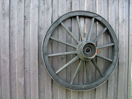 Wooden wagon wheel on an old barn door photo