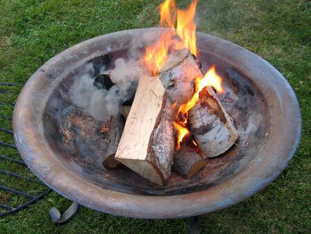 Beautiful copper fire pit bonfire with burning logs
