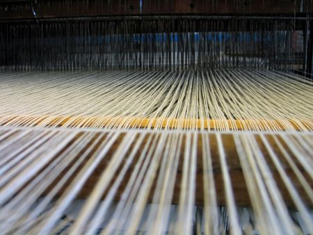 rug weaving: Strings in a handloom - All strings attached - Textile abstract Stock Photo