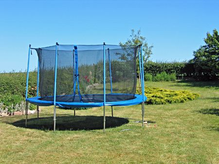 Trampoline in a back yard garden