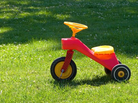 Bright colorful Tricycle standing on the grass photo