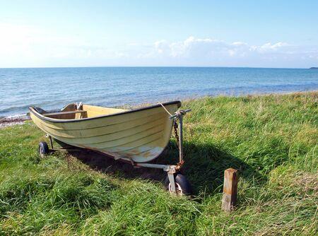 skiff: Beach landscape - small colorful skiff on the sand