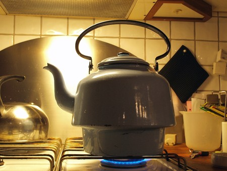 Kettle full of water boiling on a gas stove top photo