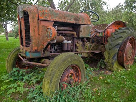 Old rusty red vintage tractor in a farm Stock Photo
