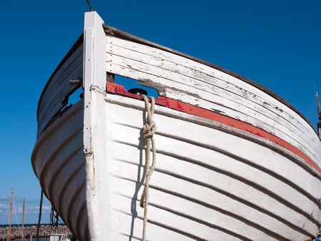 prow: Prow of a small wooden boat with clear blue sky background