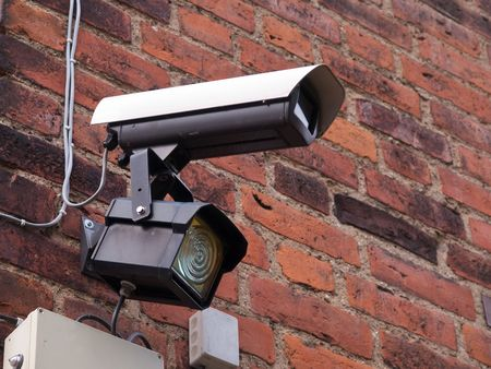 warning system: Security surveillance camera on a building corner Big Brother Stock Photo