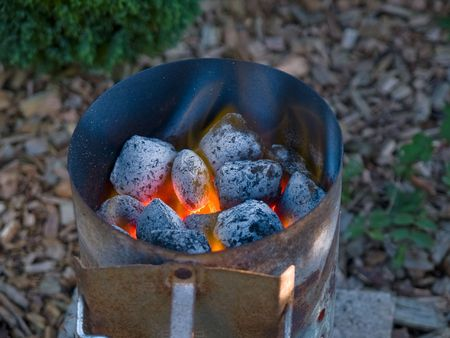 briquettes: Flaming hot red yellow charcoal briquettes in a grill starter Stock Photo