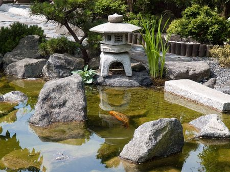 Details of Japanese garden with water pond and stone pagoda Stock Photo