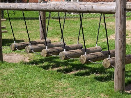 Wooden children swings in a playground park outdoors photo