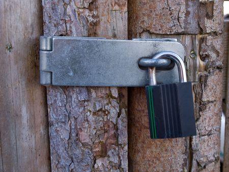 Wooden door locked with a heavy metal lock padlock Stock Photo - 6566043