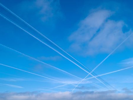 Aerial crossroad clear blue sky with crossing jets contrails traffic photo