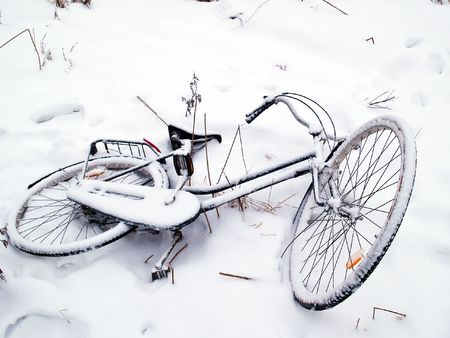 Bicycles covered with snow lay on the ground photo