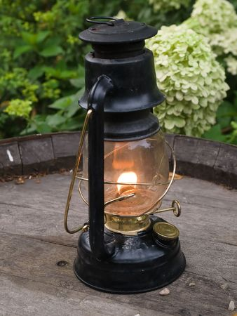 oillamp: Classical nautical oil lamp burns on a wooden barrel outdoors