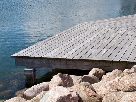 Small beautiful seaside wooden jetty dock pier deck by the ocean  photo
