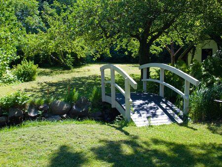 Beautiful small white wooden bridge footbridge in a garden - gardening background Stock Photo - 8336722