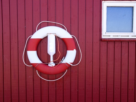 savers: Life buoy  Life Preserver  Life ring  Life belt hanged on a red painted wooden wall Stock Photo