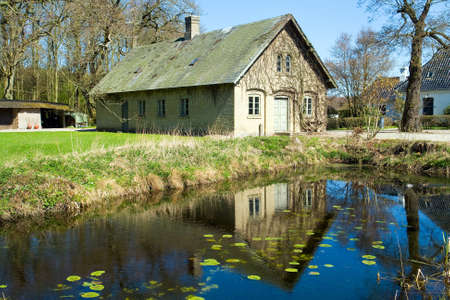 Beautiful traditional countryside style house reflected in a lake Denmark photo