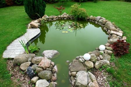 Hermoso jardín clásico diseño de los peces de estanque en el patio trasero de un fondo de jardinería bien cuidada