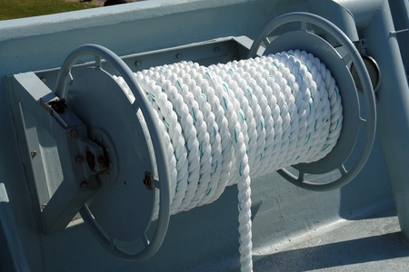 marine industry: Nautical boat rope rolled on a metal drum winch on deck Stock Photo
