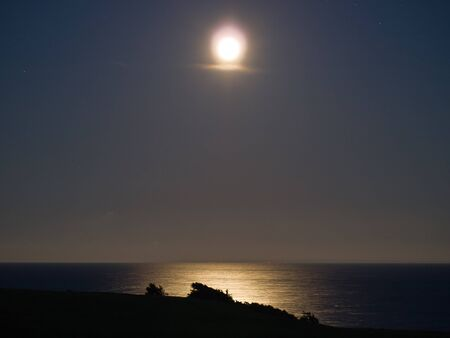 Full bright moon over the sea ocean with far away lights in the background photo