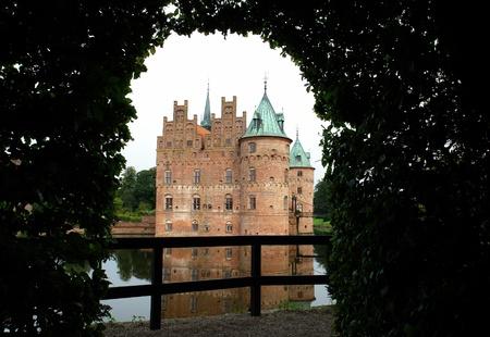 chateau:  Egeskov castle slot landmark fairy tale castle in Funen Denmark view from the garden